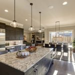 70156806 - modern gray kitchen features  dark gray cabinetry paired with white quartz countertops and a glossy gray linear tile backsplash. bar style kitchen island with granite counter. northwest, usa